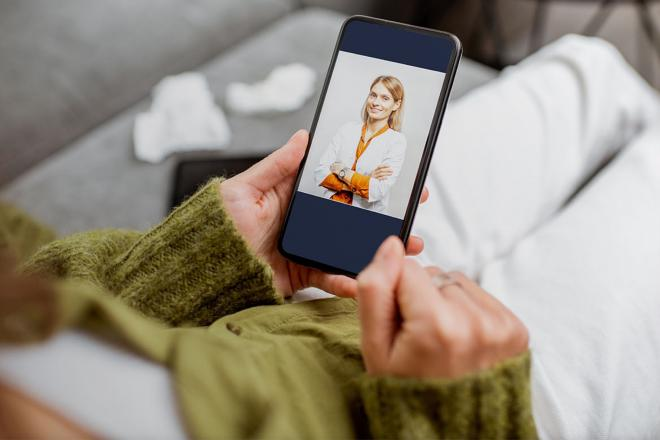 Woman holding phone with telehealth app on screen